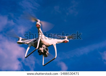 Quadcopter in flight. Unmanned aerial vehicle. Quadcopter on a blue sky background. Remote video shooting from a height. Photos and videos from above. Hobby. Intelligence equipment.