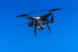 Quadrocopter with a professional camera flies in blue sky. Dron.