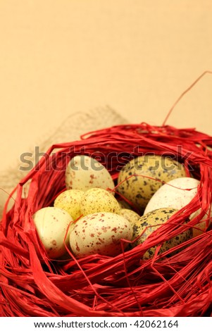 Quail Easter eggs in a red nest. Shallow DOF, copy space