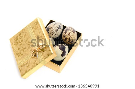 Quail eggs in a beautiful decorative golden box with a golden  ribbon on a white background