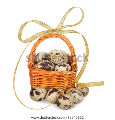 Quail eggs in basket with bow on the white background isolated