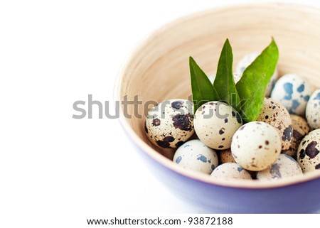 Quail eggs in bowl with leaves.