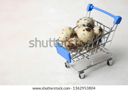 Quail eggs in grocery trolly on neutral background. Concept preparation for Easter, shopping. Copy space.