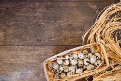 Quail eggs in nest on a wooden table. Fresh chicken eggs on a wooden rustic background. Close up of organic eggs in egg carton box, nest box. Happy Easter and natural food background.