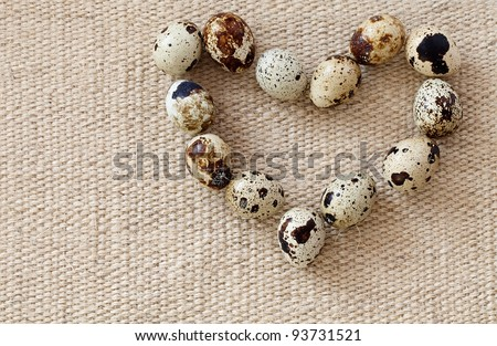 Quail eggs in the shape of heart on a sacking.