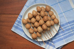 Quail eggs satay. Several hard-boiled quail eggs are put into skewers, marinated in sweet soy sauce with spices and boiled further, also served as a side-dish for soto.