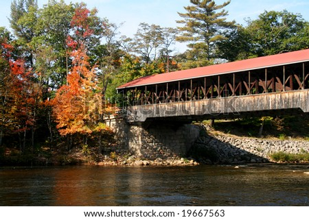 Quaint covered bridge in New England with autumn foliage