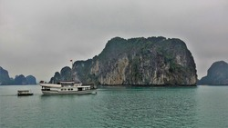 Quaint islands in the fog. Green vegetation on the steep slopes. A tourist boat is sailing on calm water. Halong Bay. Vietnam