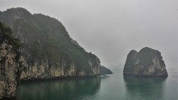 Quaint islands with steep slopes and green vegetation are surrounded by fog. Reflection on the calm water of Halong Bay. Vietnam