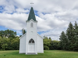 quaint little country church sitting in a green meadow surrounded by trees in the summer time