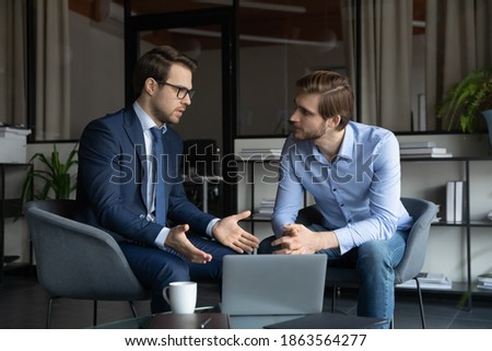 Qualified broker bank manager financial advisor and millennial man client customer discussing terms conditions of insurance contract loan agreement sitting by laptop screen on meeting in office agency