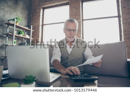 Qualified experienced intelligent confident concentrated old bearded man checking his calculations at home using calculator and netbook