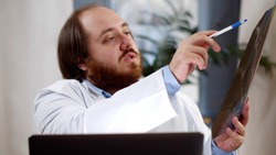 Qualified family doctor wearing coat and video-calling patient showing x-ray. Portrait of man practitioner having online consultation on laptop holding xray image and discussing diagnosis