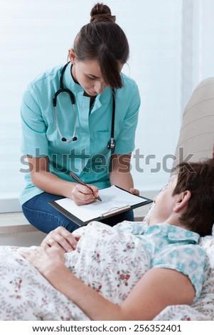 Qualified female physician prescribing the medicine to sick woman