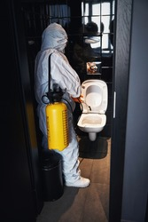 Qualified janitor doing the antiviral cleaning in the public lavatory