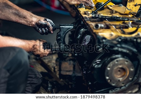 Qualified mechanic repairing hydraulic pumps, internal combustion engines, diesel engines in a car workshop. Testing engines on a dynamometer. Test stand. Oil change and engine overhaul.