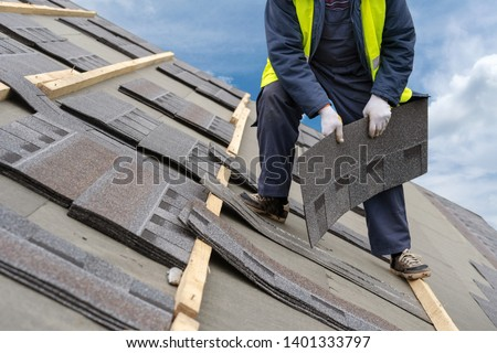 Qualified roofer worker in uniform work wear holding in hands and installing asphalt or bitumen tile on top of the roof under construction house against beautiful blue sky on background