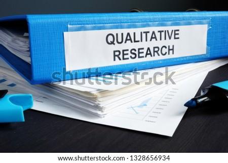 Qualitative research methods report in a blue folder. Foto d'archivio ©
