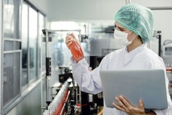 Quality control and food safety inspector test and check product contaminate standard in the food and drink factory production line with hygiene care.