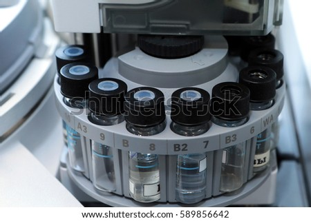 Quality Control Laboratory medicine. Chromatograph operation. Vials on autosampler of gas chromatography-mass spectrophotometer. Ampoules are chemical control suspension in the gas chromatograph