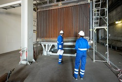 Quality control. Man and woman inspectors working in the energy industry. Blue overalls, white helmet. Operating hall and machine components. Inspection and work safety.