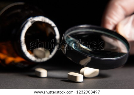 Quality control of the drug through a magnifying glass. Tablets may illustrate publications about counterfeit medicine and drug trafficking. #1232903497