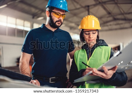 Quality Control Process Inspector writing a report in industrial factory