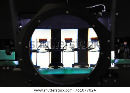 Quality Control vials for injection. Individual checks vial under a microscope. New pharmaceutical. Production of sterile medications. Pharmacology and people together. The ampoule under a microscope.