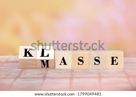 Quality instead of quantity. the cubes are turned over and the German word Masse quantity is changed to Klasse quality.