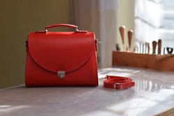 Quality luxury handmade women's bag. Women's leather handbag with a strap next to it. Red modern women's bag. A photo taken in a bag workshop.