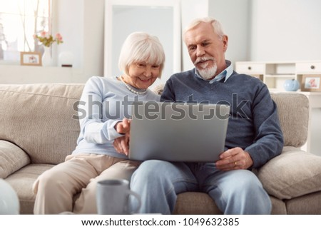 Quality time. Upbeat senior husband and wife holding a laptop in their lap and surfing the Internet together while sitting on the sofa in their living room