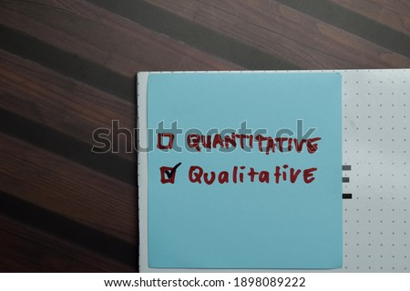 Quantitative and Qualitative write on sticky notes and supported by additional services write on a sticky notes isolated on Wooden Table. Foto d'archivio ©