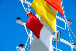 Quarantine and pilot flags flying in strong winds on a blue day on a cruise ship with navigation lights in background