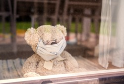 Quarantine and self isolation during coronavirus pandemic concept. Social distancing. Stay home. Soft teddy bear toy wearing medical mask sit at home looking at window