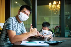 quarantine asian man and children wearing protection mask working on computer at home selected focusing on children face