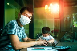 quarantine asian man and children wearing protection mask working on computer at home while covid-19 virus inflected global
