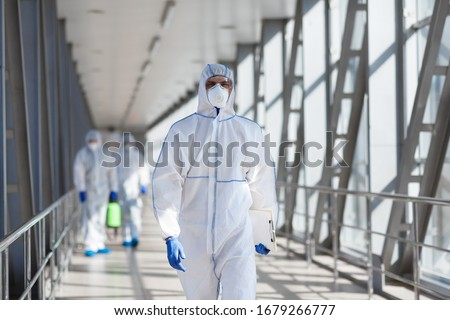 Quarantine, coronavirus infection. Disinfectant workers in protective mask and suit sprays bacterial or virus outdoor