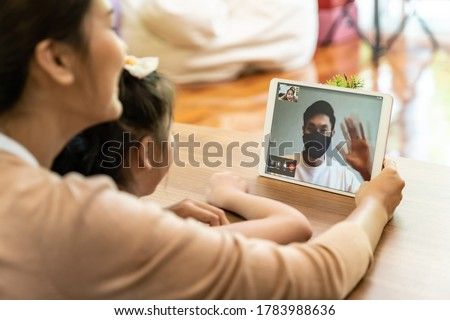 Quarantine father video conference call with his family of mom and daughter while stay in state quaratine. Technology and family reunion new normal while coronavirus covid-19 pandemic.