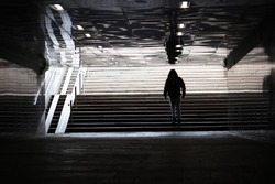 Quarantine in the city during the Covid-19 coronavirus pandemic. Black silhouette of man in medical mask walking in empty underpass