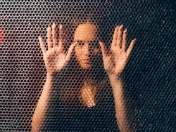 Quarantine self isolation. Pandemic anxiety. Social distancing. Textured art portrait of bored unhappy annoyed trapped woman in black touching plastic bubble wrap wall in darkness.