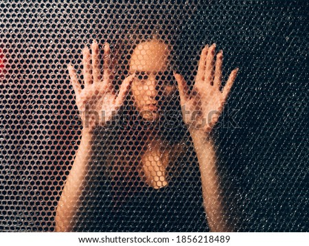 Quarantine self isolation. Pandemic anxiety. Social distancing. Textured art portrait of bored unhappy annoyed trapped woman in black touching plastic bubble wrap wall in darkness. Foto stock ©