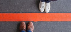 Quarantine, social distancing and differences concept. Man and woman standing opposite of each other, divided by a thick red line. Wide angle view, copy space.