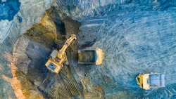 Quarry mining, work of the excavator and dump trucks, photo from the air
