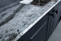 Quartz counter worktop with beautiful pattern and stainless steel sink on black wooden kitchen.
