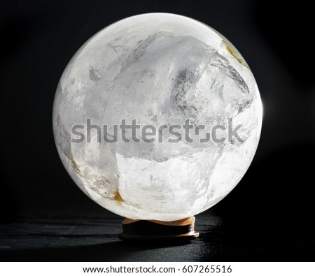 Quartz Sphere mineral spherical on a wooden base shit agains a black backdrop #607265516