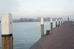 Quay along the Nieuwe Merwede with wooden bollard poles with white top in Dordrecht, the Netherlands