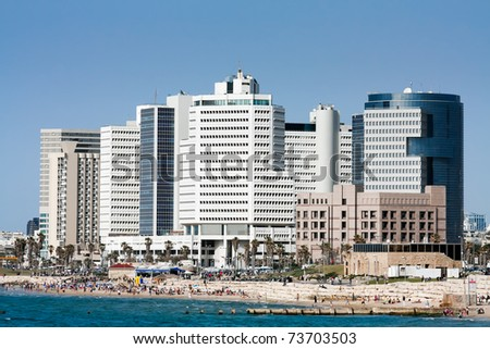 Quay of Tel Aviv with many-storeyed structures and people having a rest on seacoast