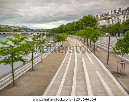 Quays of the Rhone river in the city of Lyon in the morning with a dark grey sky, green blooming trees, leading curved lines created by white stairs, and old buildings, evocking peace, quiet, resting.