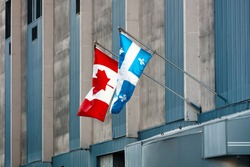Quebec and Canada flags fluttering on a building in the downtown of Montreal.