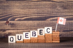 Quebec Canada. Politics, economic and immigration concept. Wooden letters and flag on the office desk